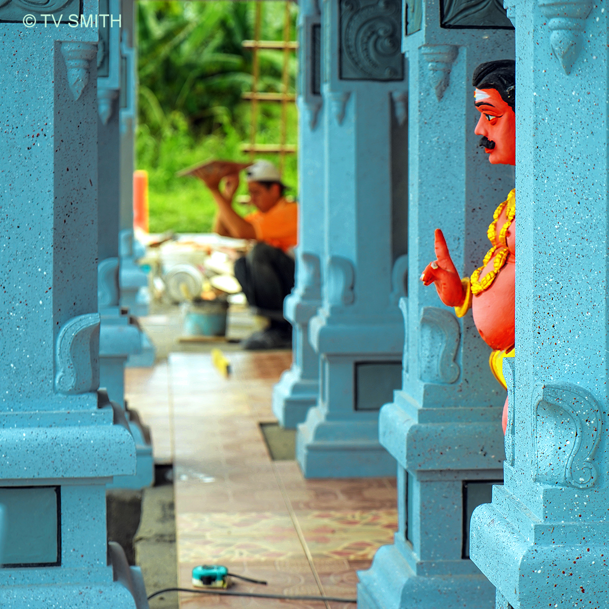 Hindu Temple Statue Supervising A Chinese Tile Installer